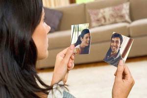 Woman with torn photograph of couple